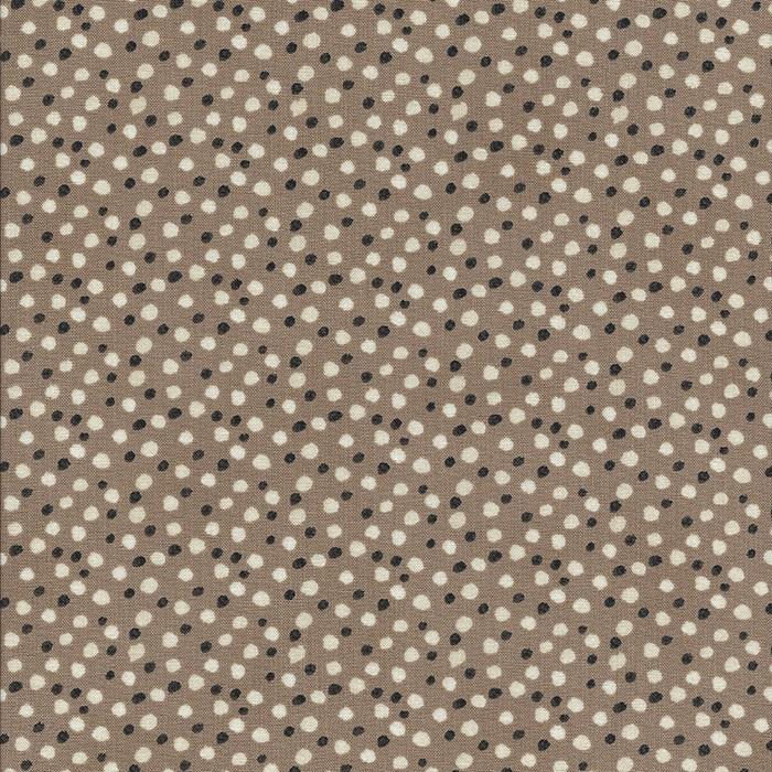 Licht bruine stof met zwarte en ecru stippen.